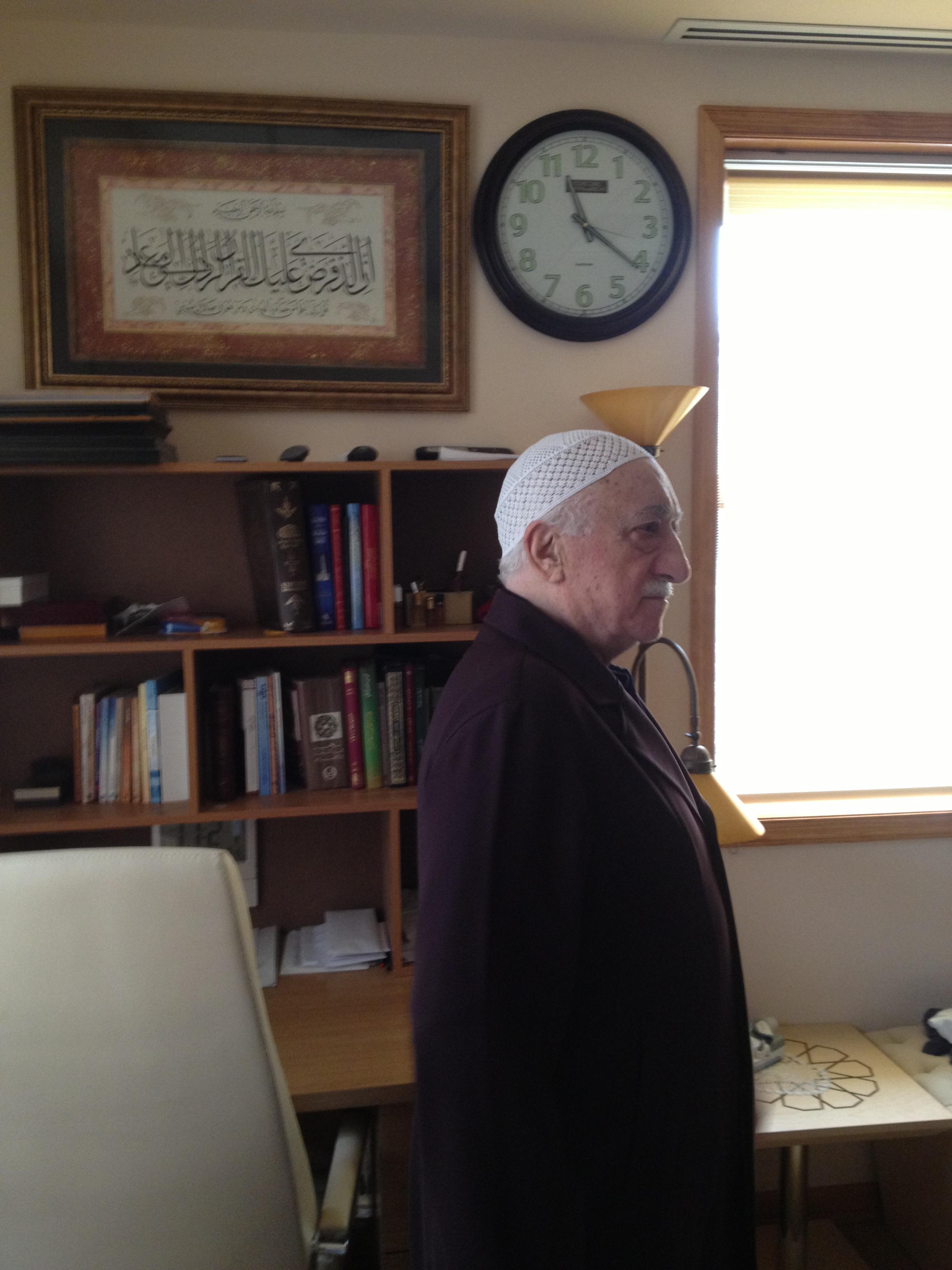 Muhterem Fethullah Gülen Hocaefendi odasındaki çalışma masasının ve Kasas Sûresi'nin 85. ayet-i kerimesini ihtiva eden tablonun önünde hat sanatındaki tecrid derinliğini anlatırken